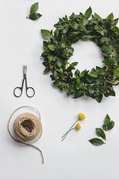 flatlay DIY midsummer flower wreath with tools on white background
