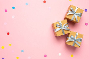 Gift or present box and color confetti on pink table with space for text. Composition for birthday,...
