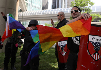 Members of the National Socialist Movement tear apart a pride flag as they demonstrate against the LGBTQ event Motor City Pride in Detroit
