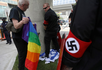 Members of the National Socialist Movement, a white nationalist group, pose over a flag of Israel as they demonstrate against the LGBTQ event Motor City Pride in Detroit, Michigan