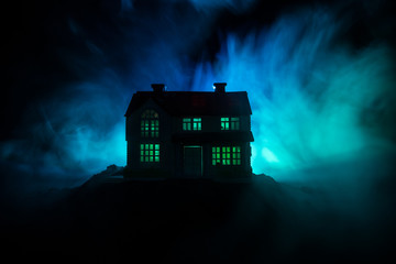 Obraz Old house with a Ghost in the forest at night or Abandoned Haunted Horror House in fog. Old mystic building in dead tree forest. Trees at night with moon. Surreal lights. - fototapety do salonu