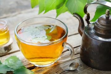 Birch leaves, healthy herbal tea cup, honey jar and vintage copper tea kettle.