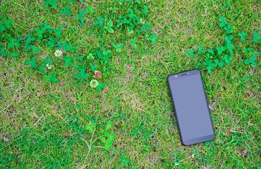 芝生やクローバーのあるところに置かれたスマートフォン、携帯電話