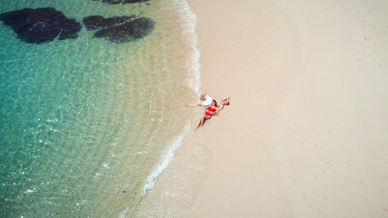 Beach drone view Phuket tropical island, white beach with waves, couple lying on the beach. Aerial Photo.