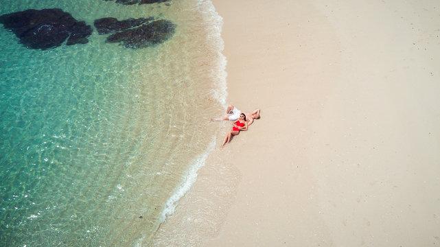 Beach drone view Phuket tropical island, white beach with waves, couple lying on the beach. Aerial Photo.