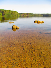 Wall Mural - Summer idyllic landscape with beautiful lake. Calm transparent water surface with stones and sandy bottom on a bright quiet day. Harmony and pacification of nature - a beautiful concept for wallpaper.