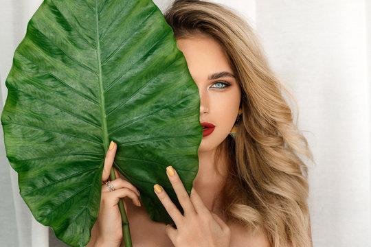 Spa and Beauty. Woman model with bright makeup and healthy skin with green leaf plant. Portrait of beautiful caucasian girl with big lips, closed eyes and sexy smile .
