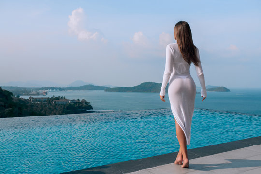view from behind on fit woman with long brown hair in a long white tight  dress looking on the infinity pool and beautiful sea. Summer vacation