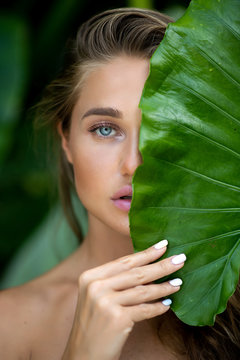 Close up: young woman with natural makeup holds a big green leaf on a blurred green background. Spa and wellness. Youth, teens and skin care concept. Close up