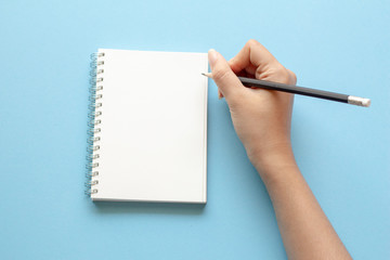 woman hands writing in empty notebook at the blue desk. Flat lay top view.