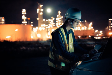 Engineer Petrochemical Asian man work late and hard with laptop computer  Inside the Refinery oil and gas Industry Factory at night.engineering Work successfully