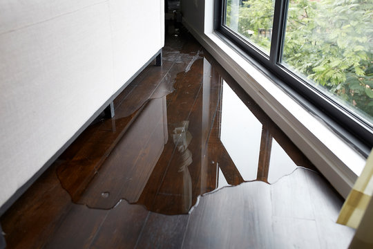 Water leaking and flooded on wood parquet floor. Room floor will damage after the water flooded.