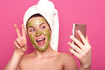 Positive charismatic young sweet lady raising two fingers making peace gesture, taking photo for beauty blog, opening mouth widely, having towel on her head, applying cosmetic green mask on face.