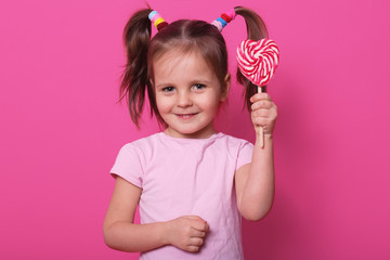 Image of sweet beautiful female child holding big lollipop candy, looks happy and excited isolated...