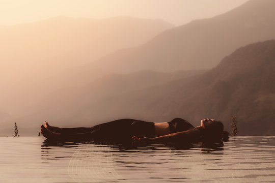 Morning light with Beautiful Attractive Asian woman practice yoga Dead Body or Savasana on the pool above the Mountain peak in front of beautiful nature views in SAPA vietnam,so comfortable,Warm Tone