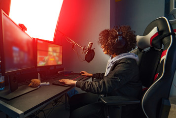 Professional Girl Gamer Plays in Video Game on Her Computer. She's Participating in Online Cyber Games Tournament, Plays at Home, or in Internet Cafe. She Wears Gaming Headset
