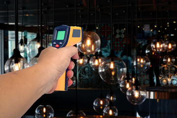 Yellow Infrared thermometer gun in hand used to measure temperature  on background.