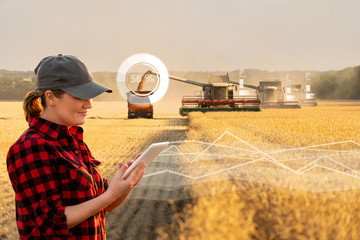Wall Mural - Woman farmer with digital tablet on a background of harvesters. Smart farming concept.