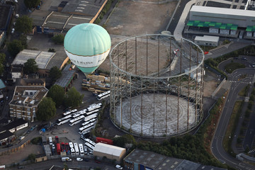 A hot air balloon flies over a gas holder during the Lord Mayor's Hot Air Balloon Regatta, in London