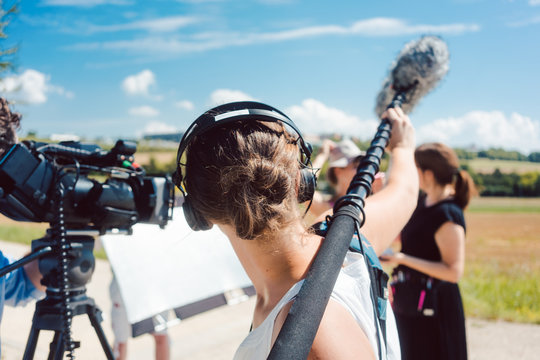 Woman holding microphone on a boom during video production