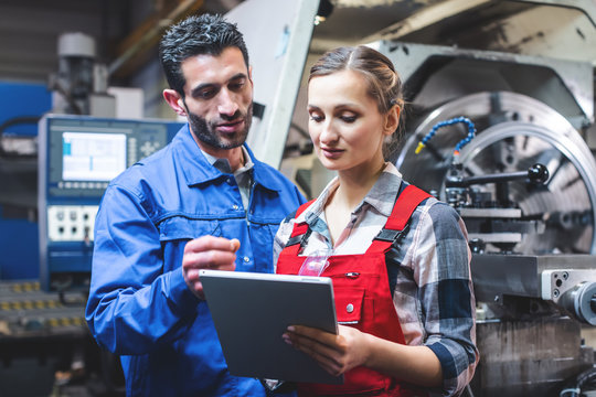 Woman and man manufacturing worker in discussion