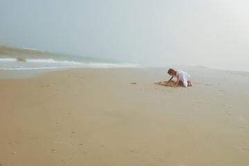 Girl playing in sand near ocean on beach