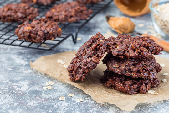Flourless no bake peanut butter and oatmeal chocolate cookies on  parchment, horizontal, copy space