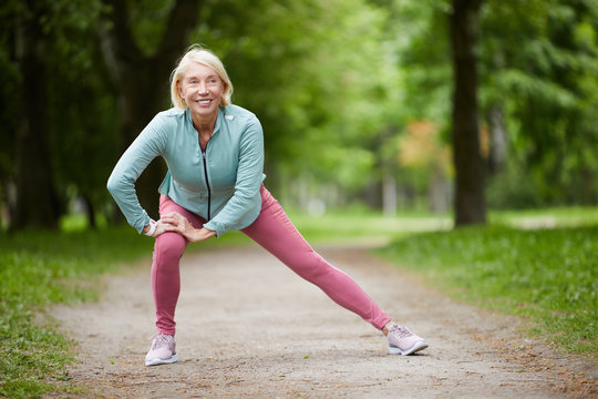 Contemporary mature blonde female in activewear doing exercise for leg stretch while enjoying workout in natural environment
