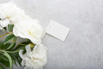 Beautiful white peony flowers and tag on gray stone background.
