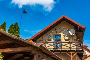 Obraz The facade of the second floor of the house with a wooden balcony - fototapety do salonu