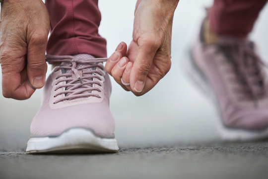 Hands of mature sportswoman tying shoelace of right cross-shoe while getting ready for jogging or working out on stadium