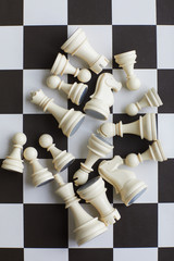 Randomly scattered lying white wooden chess pieces in center of black and white chess board