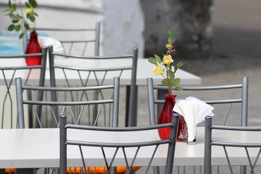 Vase with yellow roses on the table in a street cafe, outdoor