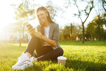 Image of beautiful stylish woman sitting on green grass with a phone in hand and coffee. She is talking on the phone through wireless headphones. Sunset light. Lifestyle concept.