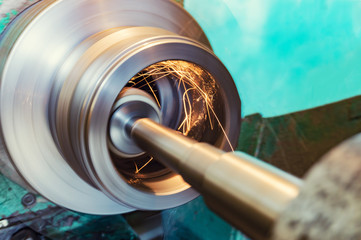 Internal grinding of a cylindrical part with an abrasive wheel on a machine, sparks fly in different directions. Metal machining. Wall mural