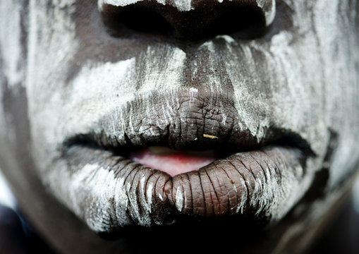 Close up on a mursi tribe woman mouth with face paint in mago national park, Omo valley, Ethiopia