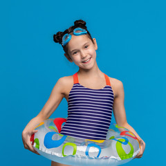 Little girl wearing inflatable ring and swim goggles