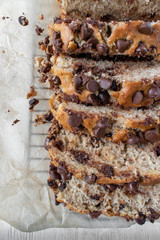 sliced chocolate chip banana bread loaf on wax paper flat lay