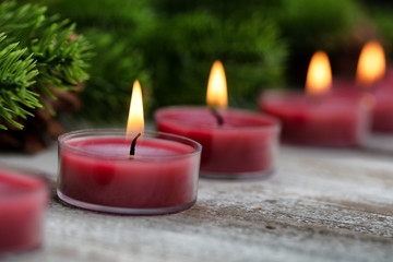 Close up view of traditional glowing Christmas holiday candles with evergreen in background