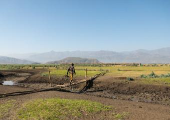 Ethiopian man crossing a wooden bridge in an artuma tribe village, Amhara region, Kemise, Ethiopia