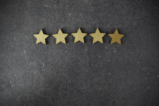 five golden stars on dark background, top rating concept