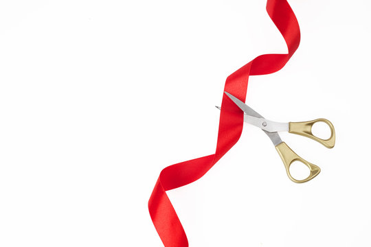 Grand opening. Top view of gold scissors cutting red ribbon on wite background.