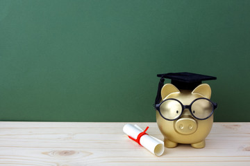 Gfold piggy bank with a grad cap and diploma in front of green chalkboard. Education scholarship