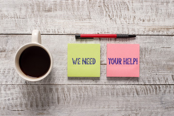 Text sign showing We Need Your Help. Business photo text asking someone to stand with you against difficulty Stationary placed next to a cup of black coffee above the wooden table