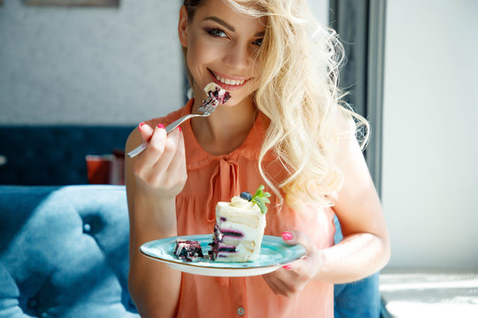 A beautiful woman in a cafe is drinking coffee and eating a cake.