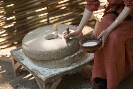 Woman grinds wheat and makes flour on millstone
