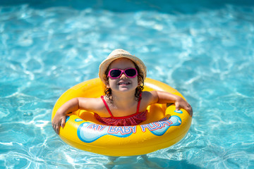 Child In Swimming Pool with ring. Summer Vacation With Kids.