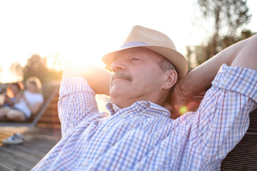 Old hispanic man sits on bench, smiling, enjoying summer sunny day. All problems left behind. Concept of happy retired person Wall mural