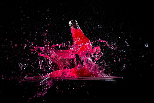red water glass bottle got shot and explosion splash fracture in dark background for energy drink stock photo