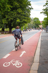 Man cycling along a marked bicycle lane, holding extra extra bicycle tires